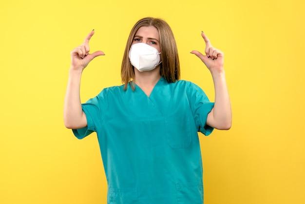 Vooraanzicht vrouwelijke arts die masker op gele ruimte draagt
