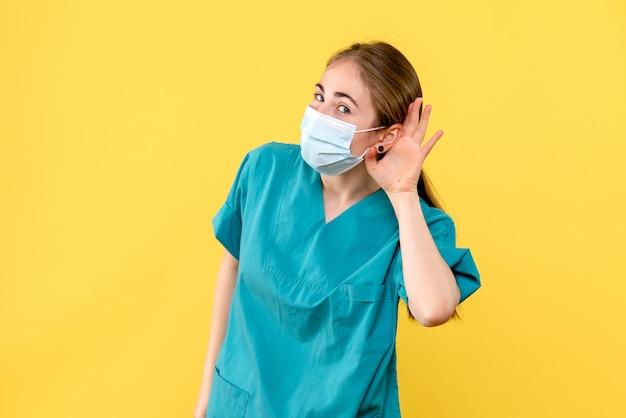 Vooraanzicht vrouwelijke arts die op gele achtergrond pandemisch covid gezondheidsvirus luistert