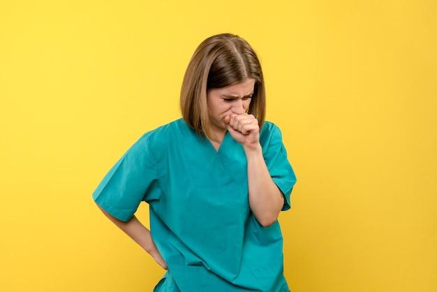 Vooraanzicht vrouwelijke arts die op gele ruimte hoest