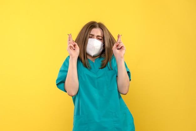 Vooraanzicht vrouwelijke arts die op gele ruimte hoopt