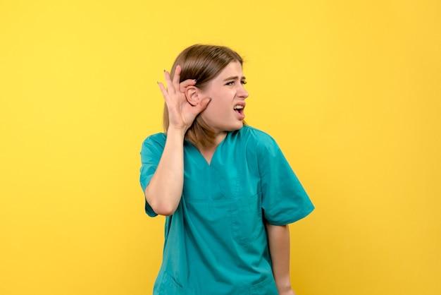 Vooraanzicht vrouwelijke arts die op gele ruimte probeert te luisteren