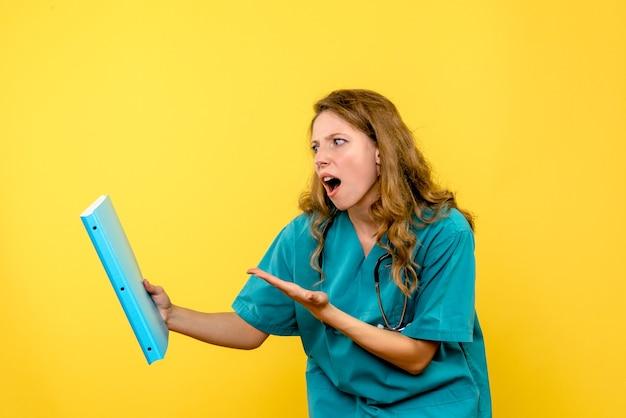 Vooraanzicht vrouwelijke arts die op gele ruimte wordt verward