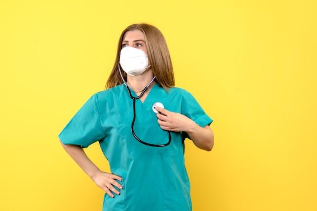Vooraanzicht vrouwelijke arts die steriel masker op gele ruimte draagt