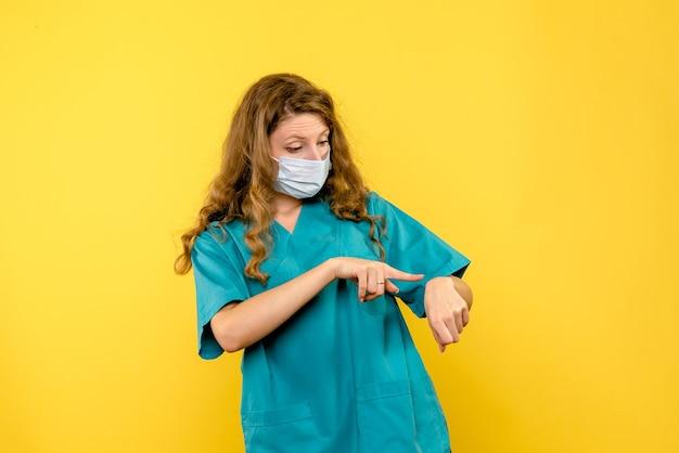 Vooraanzicht vrouwelijke arts die tijd op gele ruimte controleert