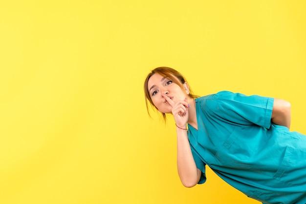 Vooraanzicht vrouwelijke arts die vraagt om op gele ruimte te zwijgen