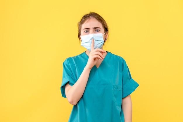 Vooraanzicht vrouwelijke arts die vraagt om stilte te houden op gele achtergrond pandemie ziekenhuisgezondheid