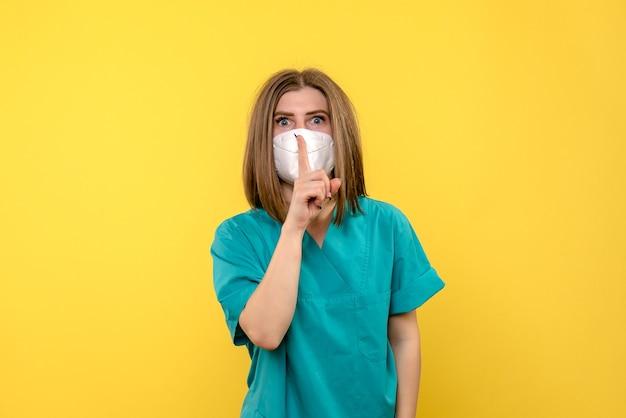 Vooraanzicht vrouwelijke arts die vraagt stil te zijn op gele ruimte
