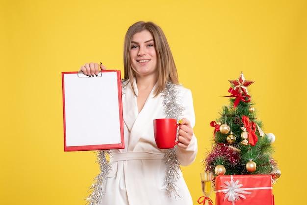Vooraanzicht vrouwelijke arts dossier nota en kopje thee te houden