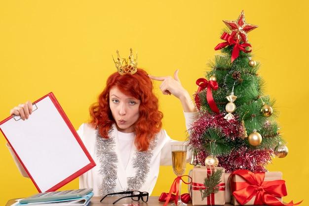 Vooraanzicht vrouwelijke arts dossiernota rond kerstboom en cadeautjes te houden