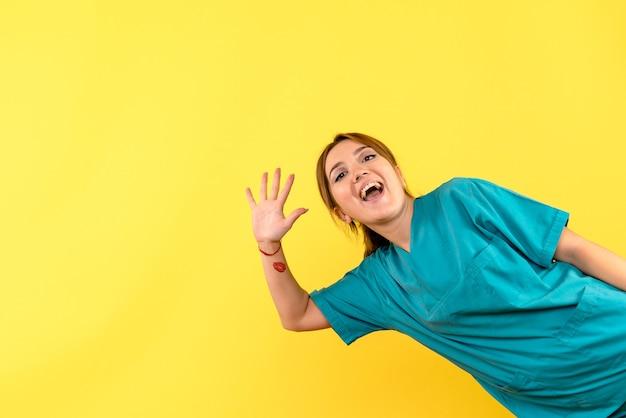 Vooraanzicht vrouwelijke arts groet op gele ruimte