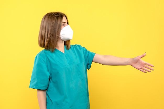 Vooraanzicht vrouwelijke arts handen schudden op gele ruimte