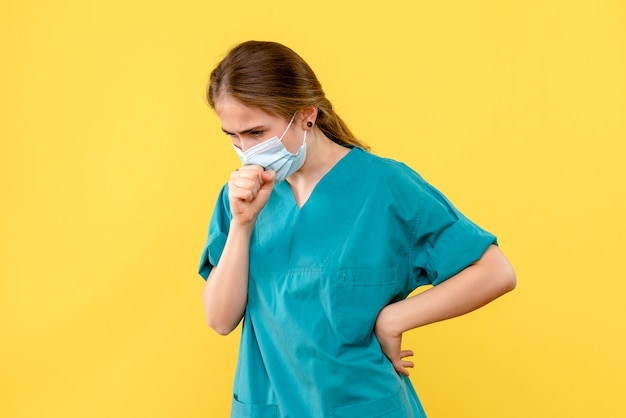Vooraanzicht vrouwelijke arts hoesten op gele achtergrond covid-health ziekenhuis pandemie