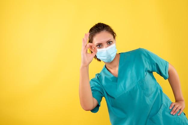 Vooraanzicht vrouwelijke arts in beschermend masker op gele achtergrond