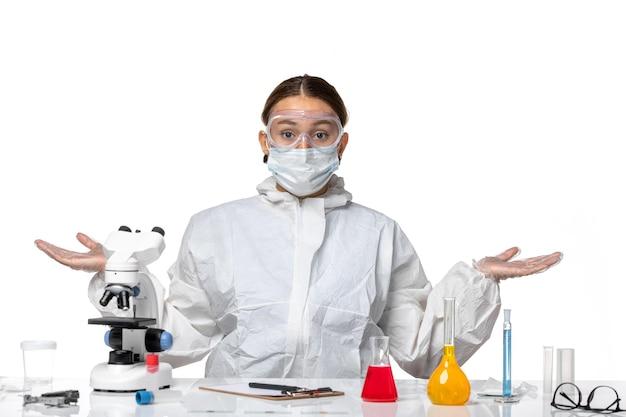 Vooraanzicht vrouwelijke arts in beschermend pak en met masker zittend met oplossingen op wit bureau virus covid-gezondheid pandemie