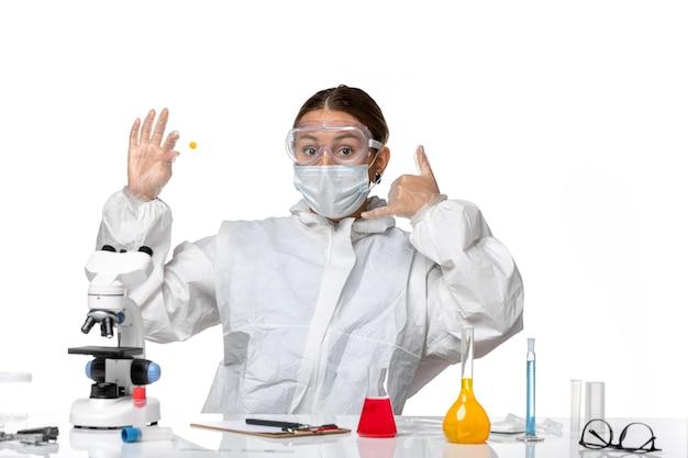 Vooraanzicht vrouwelijke arts in beschermend pak en met monster van de maskerholding op lichte witte achtergrond geneeskunde covid-pandemisch virus