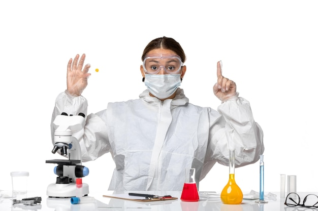 Vooraanzicht vrouwelijke arts in beschermend pak en met monster van de maskerholding op witte achtergrond geneeskunde covid-gezondheid pandemisch virus