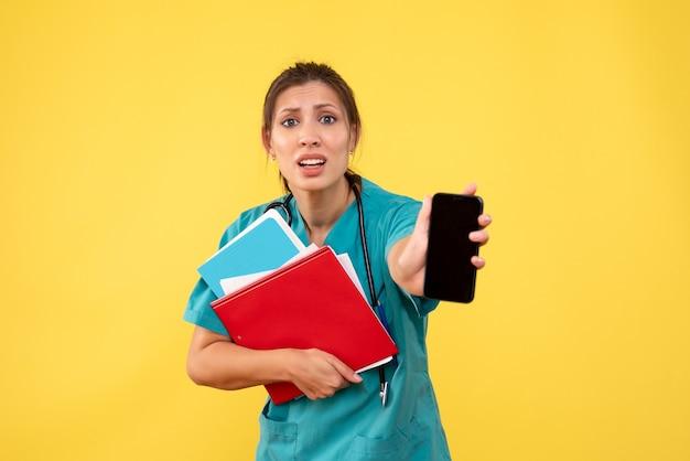 Vooraanzicht vrouwelijke arts in de medische analyse van de overhemdsholding en telefoon op gele achtergrond