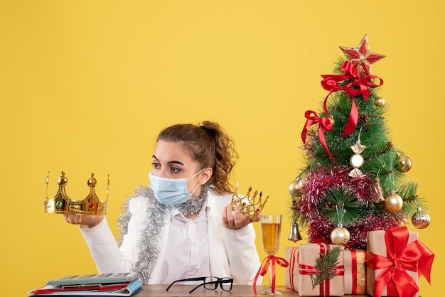 Vooraanzicht vrouwelijke arts in de steriele kronen van de maskerholding