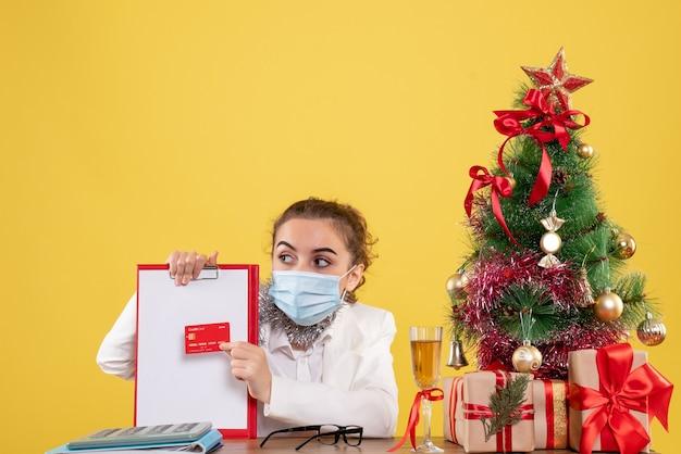 Vooraanzicht vrouwelijke arts in het dossiernota en de bankkaart van de maskerholding