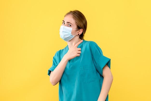 Vooraanzicht vrouwelijke arts in masker op gele achtergrond gezondheid ziekenhuis pandemie covid