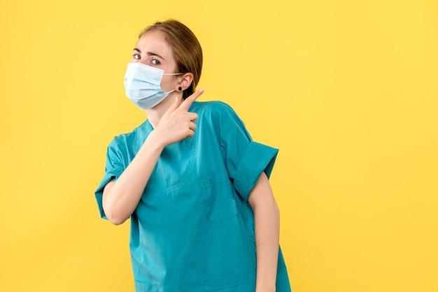 Vooraanzicht vrouwelijke arts in masker op gele achtergrond pandemisch covid gezondheidsvirus