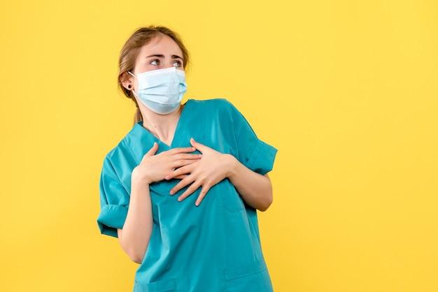 Vooraanzicht vrouwelijke arts in masker op gele achtergrond ziekenhuis gezondheid covid-pandemie