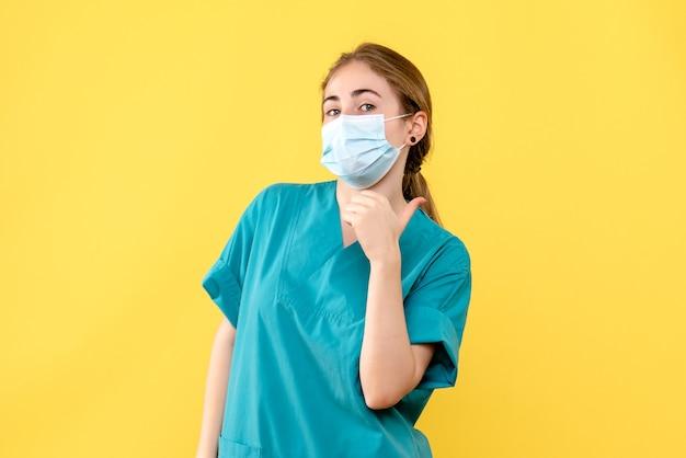 Vooraanzicht vrouwelijke arts in masker op gele bureau gezondheid ziekenhuis pandemie covid