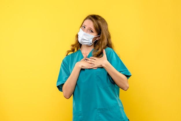 Vooraanzicht vrouwelijke arts in masker op gele ruimte