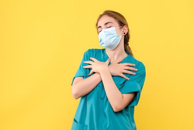 Vooraanzicht vrouwelijke arts in masker op het gele bureau de gezondheid van het ziekenhuis covid-pandemie