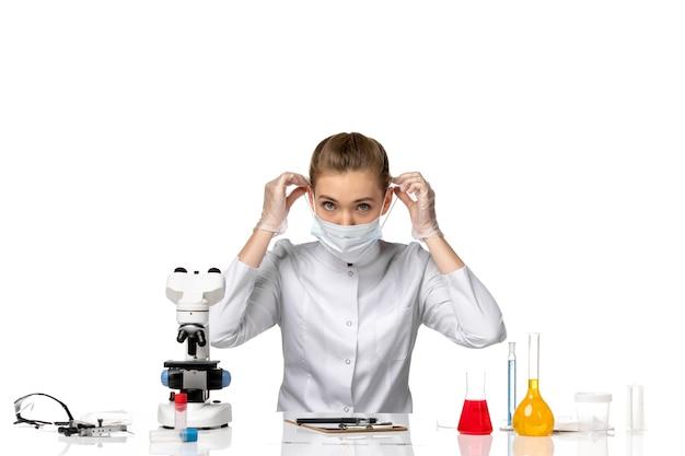 Vooraanzicht vrouwelijke arts in medisch kostuum die masker dragen wegens covid op witte ruimte