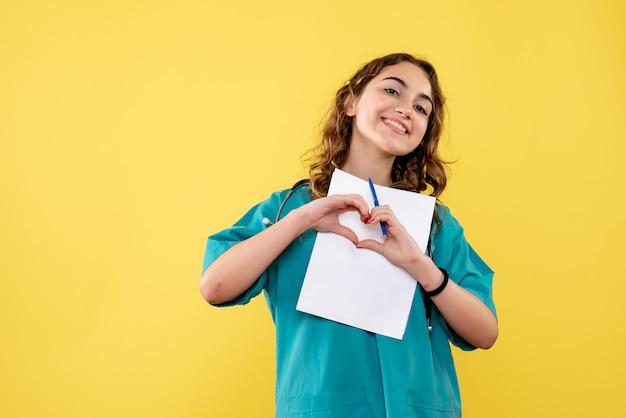 Vooraanzicht vrouwelijke arts in medisch overhemd analyse op geel bureau uniform covid-19 gezondheid emotie pandemisch virus te houden