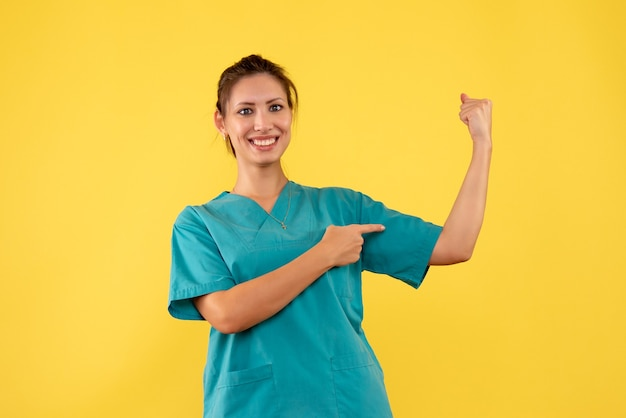 Vooraanzicht vrouwelijke arts in medisch overhemd buigen op een gele achtergrond
