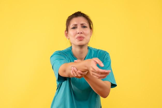 Vooraanzicht vrouwelijke arts in medisch overhemd deed pijn aan haar hand op gele achtergrond