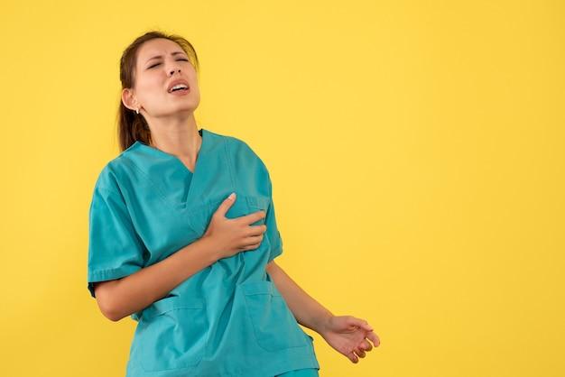 Vooraanzicht vrouwelijke arts in medisch overhemd die aan hartzeer op gele achtergrond lijden