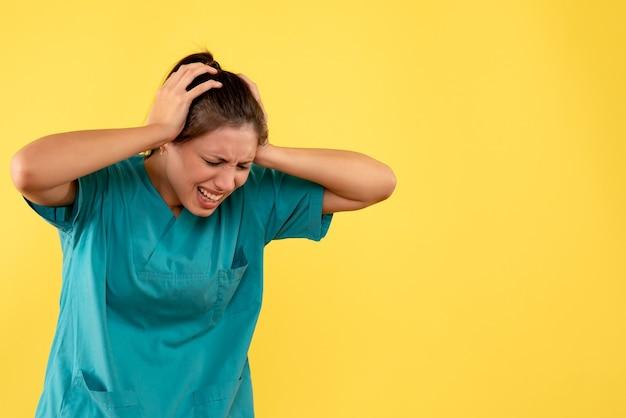 Vooraanzicht vrouwelijke arts in medisch overhemd die aan hoofdpijn op gele achtergrond lijdt