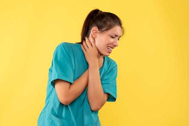 Vooraanzicht vrouwelijke arts in medisch overhemd die aan keelpijn op gele achtergrond lijden