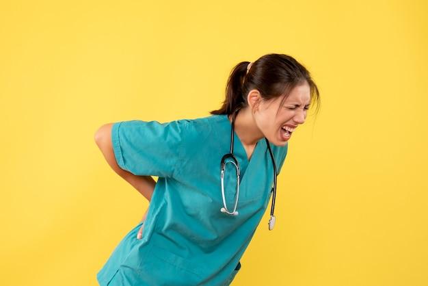 Vooraanzicht vrouwelijke arts in medisch overhemd die aan rugpijn op gele achtergrond lijden