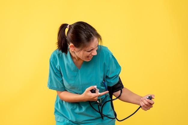 Vooraanzicht vrouwelijke arts in medisch overhemd die haar druk op gele achtergrond controleren
