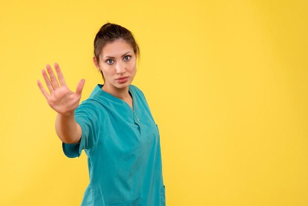 Vooraanzicht vrouwelijke arts in medisch overhemd die op de gele achtergrond vraagt om te stoppen
