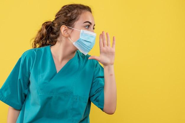 Vooraanzicht vrouwelijke arts in medisch overhemd en masker bellen, virus pandemie uniform covid-19 gezondheid coronavirus