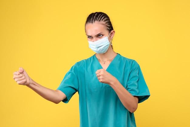 Vooraanzicht vrouwelijke arts in medisch overhemd en masker boos, gezondheidsverpleegster ziekenhuisvirus covid-19 pandemische kleur