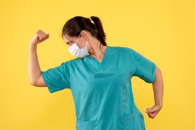 Vooraanzicht vrouwelijke arts in medisch overhemd en masker buigen op gele achtergrond