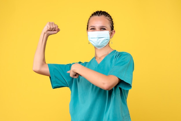 Vooraanzicht vrouwelijke arts in medisch overhemd en masker buigen, virus gezondheid verpleegkundige ziekenhuis covid-19 pandemische kleur