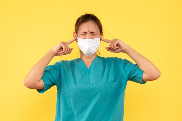 Vooraanzicht vrouwelijke arts in medisch overhemd en masker dat haar oren op gele achtergrond sluit