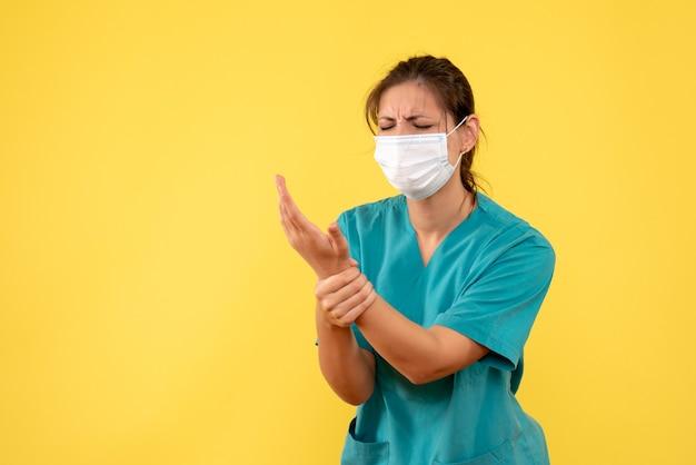 Vooraanzicht vrouwelijke arts in medisch overhemd en masker deed pijn aan haar hand op gele achtergrond