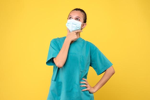 Vooraanzicht vrouwelijke arts in medisch overhemd en masker denken, gezondheidsverpleegster virus pandemie ziekenhuis covid-19 medic