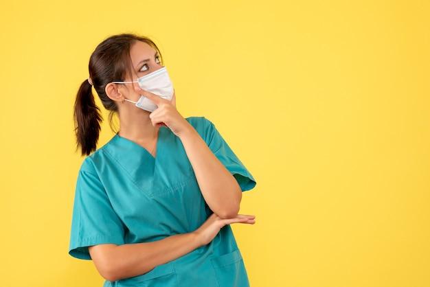Vooraanzicht vrouwelijke arts in medisch overhemd en masker die op de gele achtergrond denken