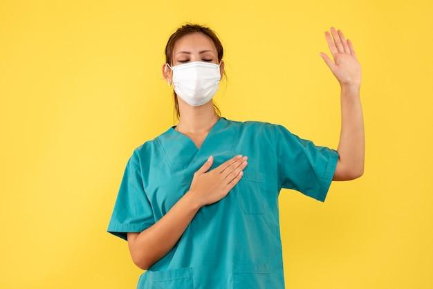 Vooraanzicht vrouwelijke arts in medisch overhemd en masker die op gele achtergrond vloeken