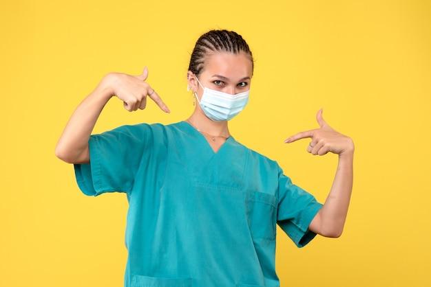 Vooraanzicht vrouwelijke arts in medisch overhemd en masker, dokter gezondheid verpleegster virus pandemie covid-19 ziekenhuis