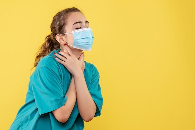 Vooraanzicht vrouwelijke arts in medisch overhemd en masker, gezondheid covid-19 pandemische kleur uniform